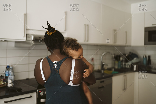 Mother carrying toddler into the kitchen