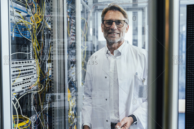 Male IT professional standing by network server in date center seen through glass