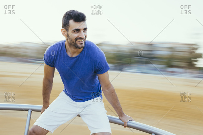 Smiling young man standing on spinning carousel against clear sky
