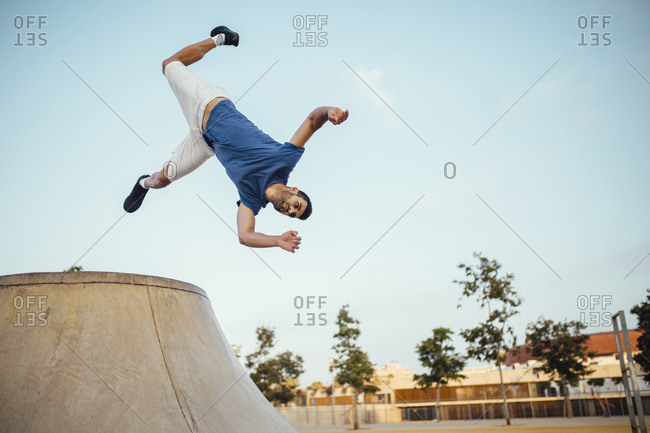 Young man jumping while performing stunt against sky in city
