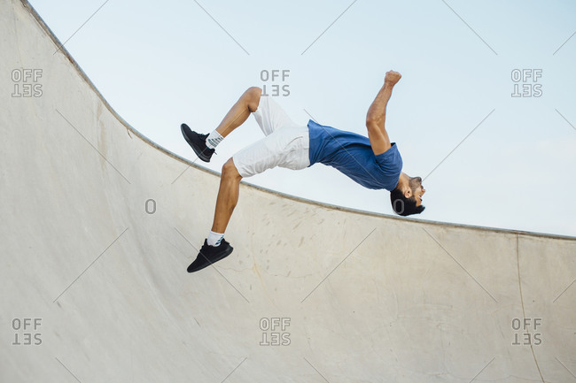 Young man doing wallflip on sports ramp against sky