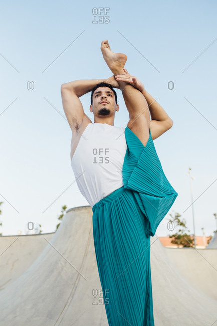 Young man splitting leg while practicing rhythmic gymnastics against clear sky