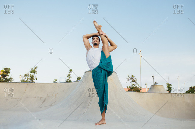 Confident man splitting leg while practicing rhythmic gymnastics against clear sky