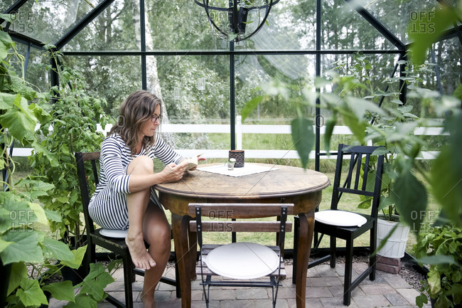 Woman reading in a greenhouse