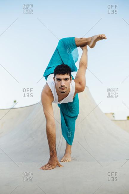 Confident young man practicing rhythmic gymnastics on sports ramp against clear sky