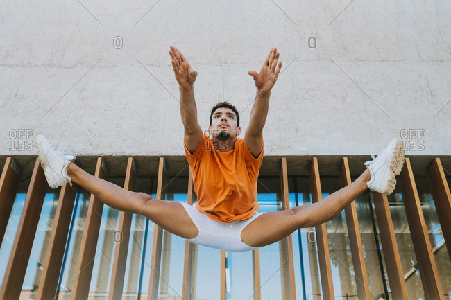 Young man with legs apart jumping against built structure