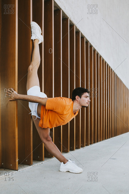 Young man doing rhythmic gymnastics exercise by built structure in city