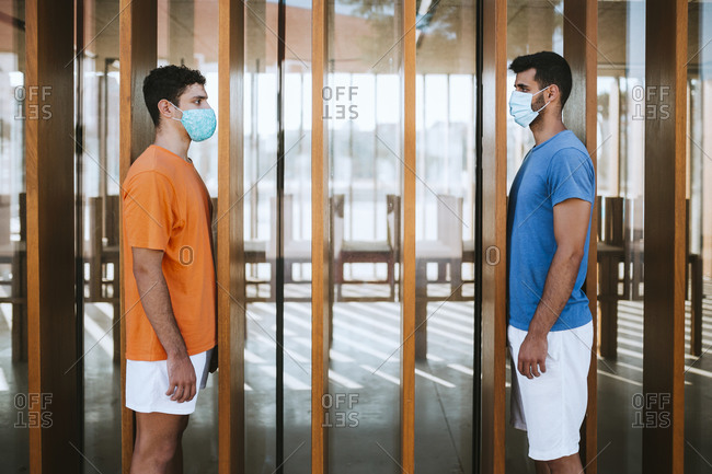 Male friends wearing masks looking at each other while standing by built structure
