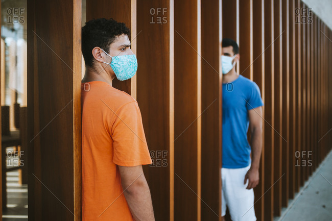 Male friends wearing masks standing by wooden built structure in city