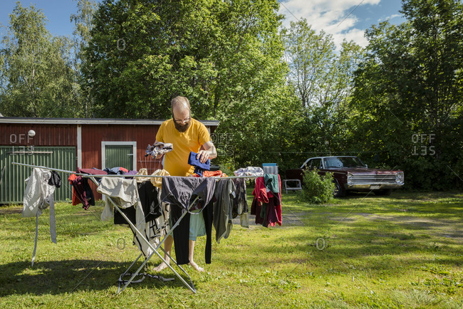 Man hanging laundry in the yard