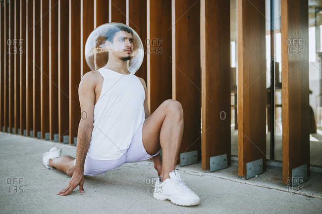 Young man wearing glass container on head exercising against built structure