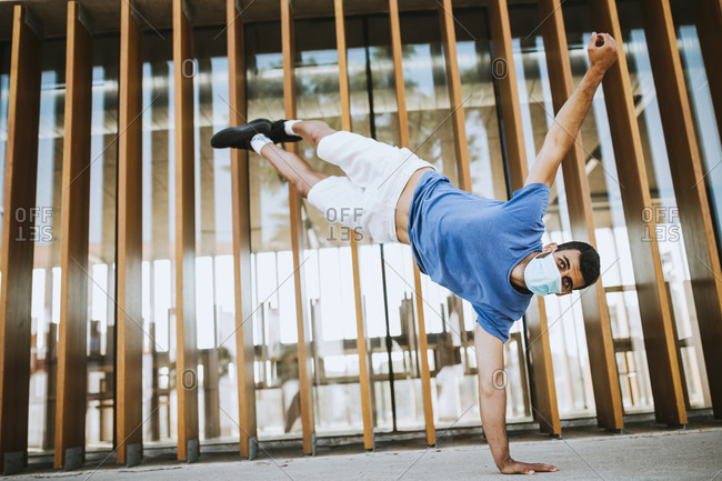 Young man wearing mask doing handstand against built structure