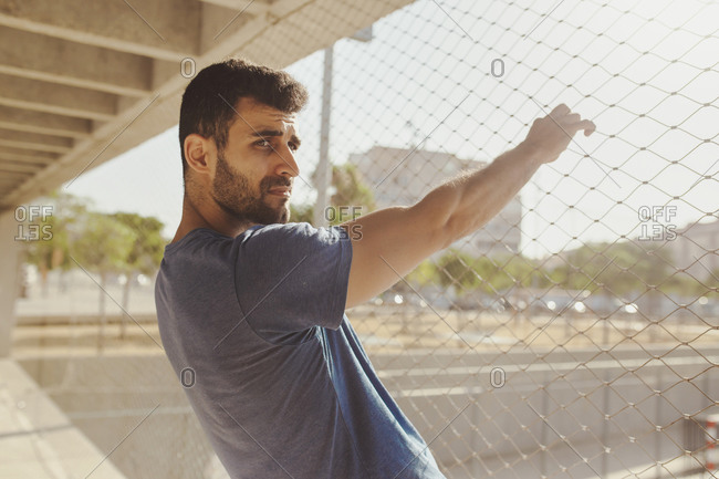 Young man holding chain-link fence during sunny day