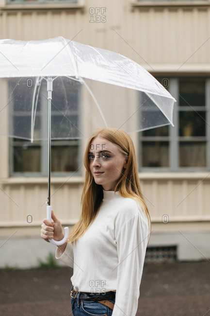Smiling woman holding an umbrella