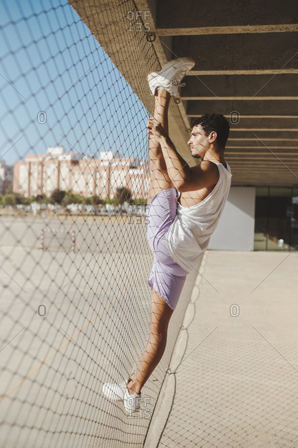 Young man doing rhythmic gymnastic exercise by chain-link fence