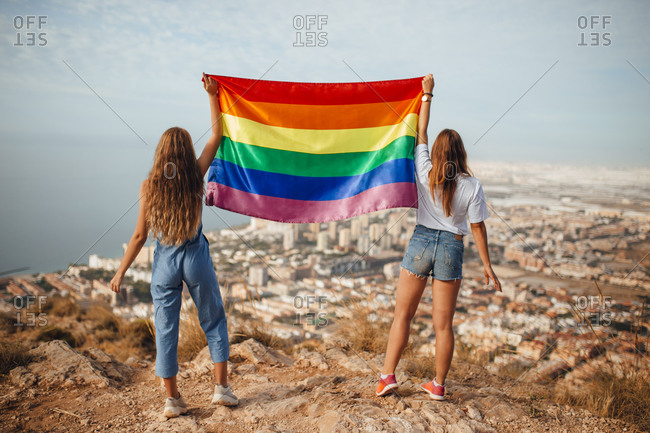 Two young women with an LGBT flag above the coastal city of Almeria- Spain