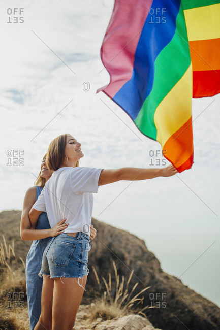 Two young women having fun with an LGBT flag
