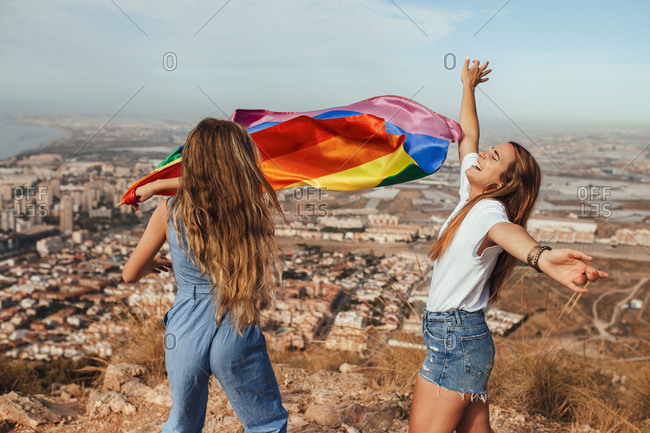 Two cheerful young women with an LGBT flag above the coastal city of Almeria- Spain