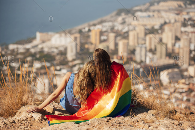 Two young women with an LGBT flag sitting on a cliff above the coastal city of Almeria- Spain