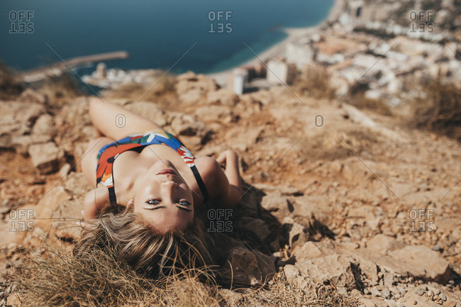 Young woman in swimsuit lying on a cliff above the coastal city of Almeria- Spain