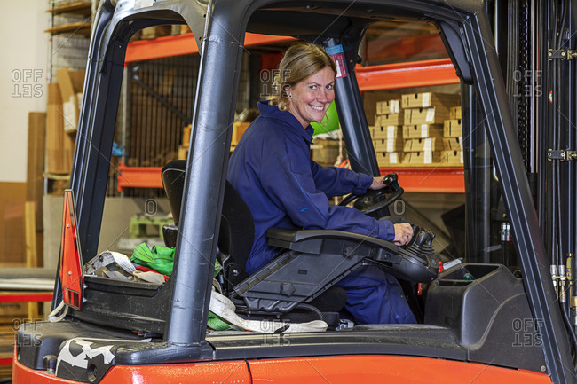 Woman driving forklift truck in warehouse
