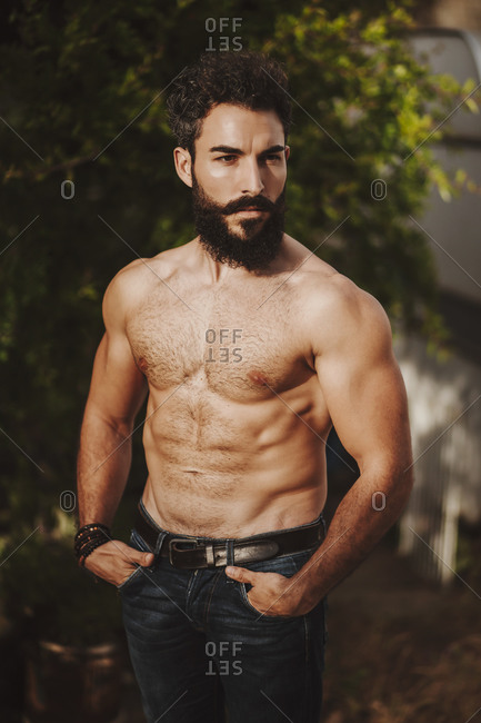 Attractive shirtless man standing in front of shrubs