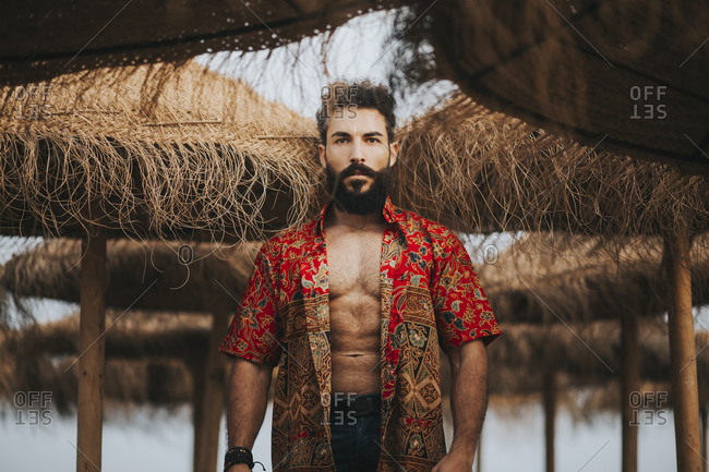 Attractive bearded man with colorful shirt standing between beach umbrellas