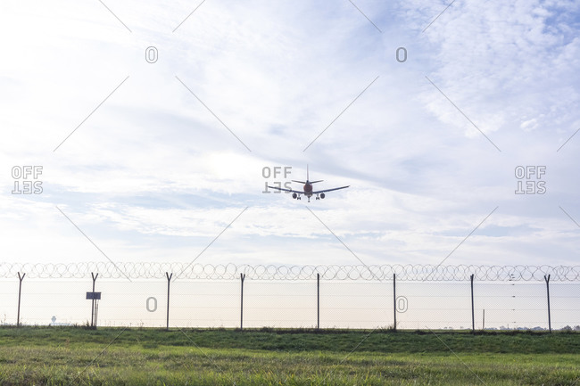 Airplane preparing to land over wire fence