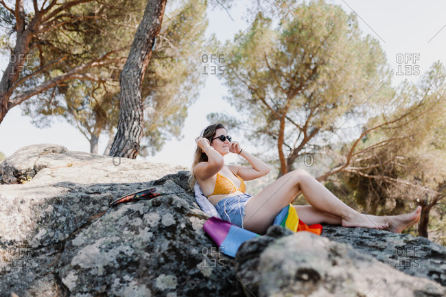 Young woman wearing sunglasses with rainbow flag relaxing on rock against trees