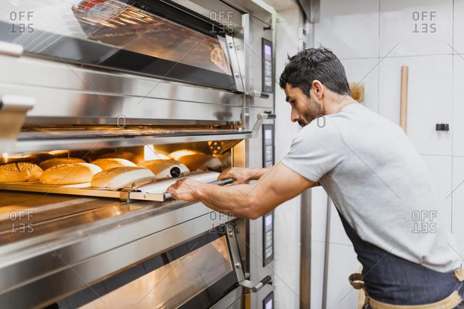 Baker baking bread at bakery