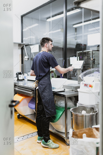 Young baker working at kitchen counter in bakery