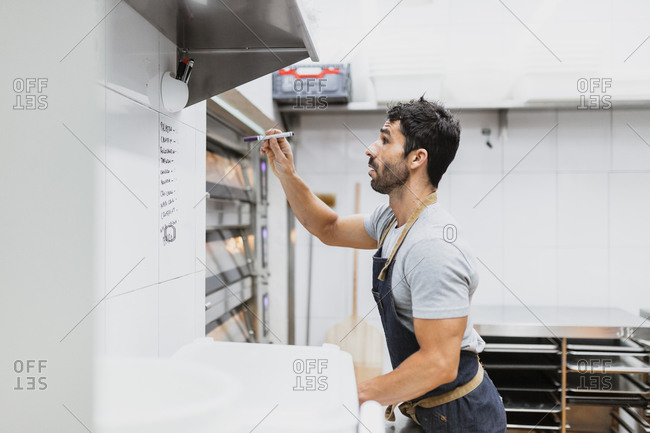 Baker writing with pen on wall in bakery