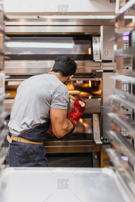 Male baker baking bread in oven at bakery