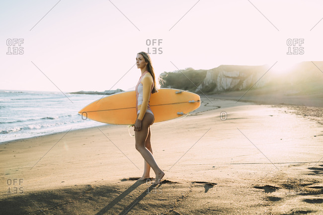 Young woman wearing wetsuit carrying surfboard at beach during sunset