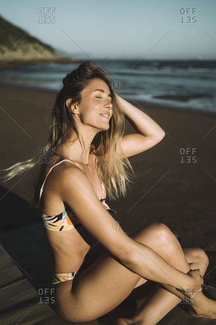 Smiling young woman wearing bikini with hand in hair sitting at beach during sunset