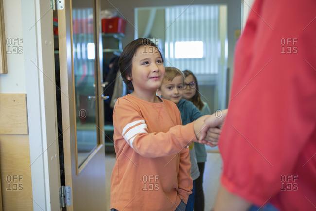 Boy shaking his teacher's hand