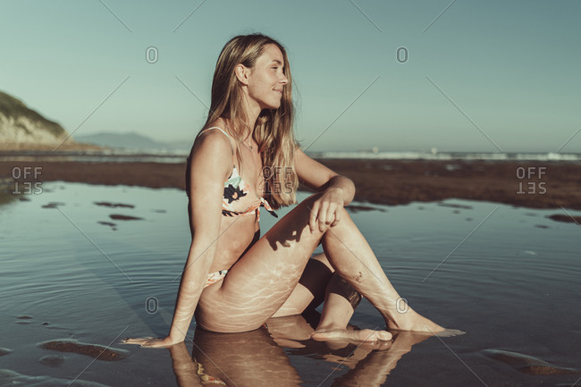 Thoughtful woman wearing bikini sitting in sea against clear sky at sunset