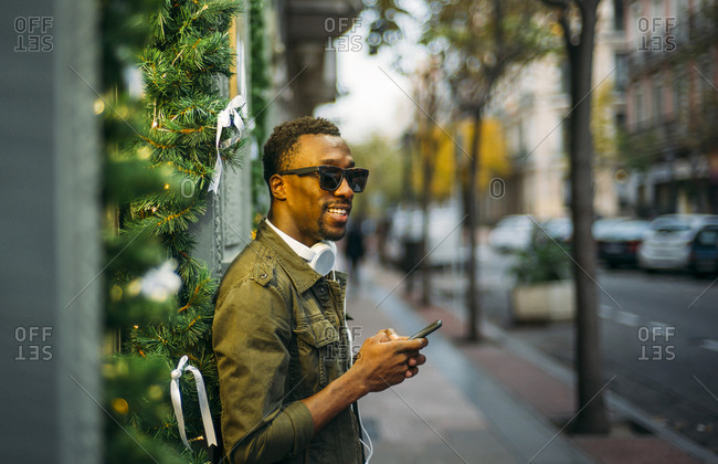 Young man wearing sunglasses using smart phone while standing on sidewalk in city