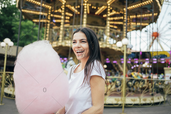 Cheerful young woman with cotton candy standing in amusement park