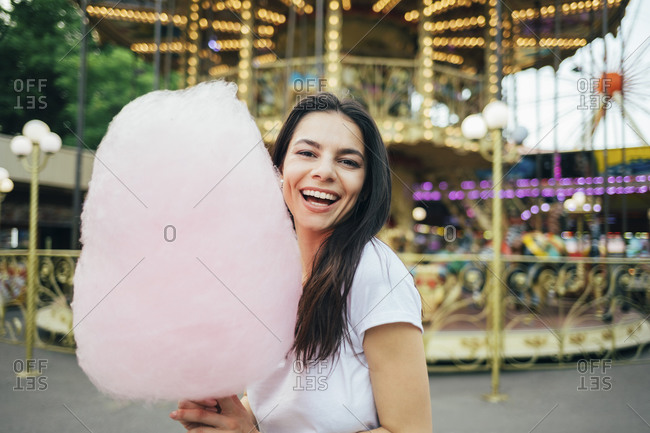 Cheerful beautiful woman holding cotton candy standing against carousel in amusement park
