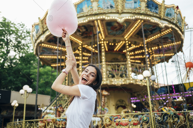 Cheerful beautiful woman holding cotton candy screaming while standing in amusement park