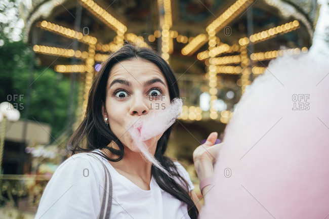 Close-up of young woman eating cotton candy against carousel in amusement park