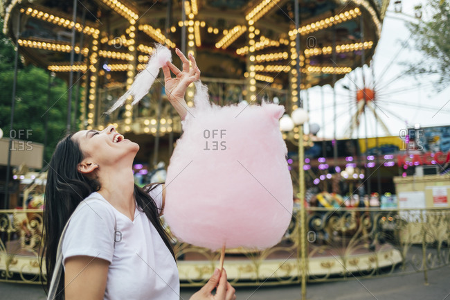 Happy beautiful woman eating cotton candy while standing against carousel in amusement park