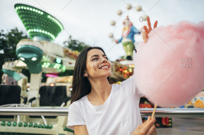 Smiling young woman holding cotton candy while standing at amusement park