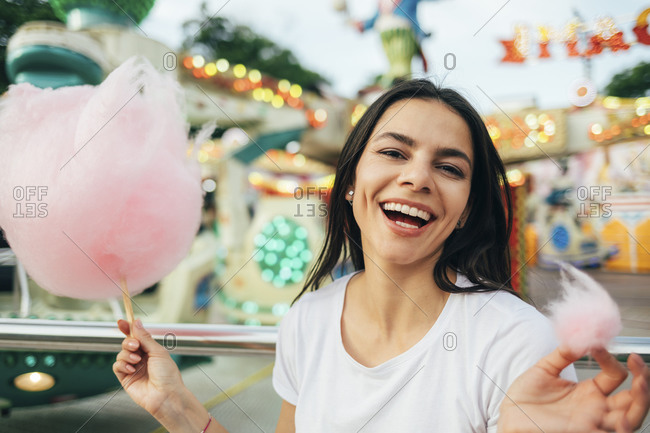 Close-up of beautiful woman holding cotton candy laughing in amusement park