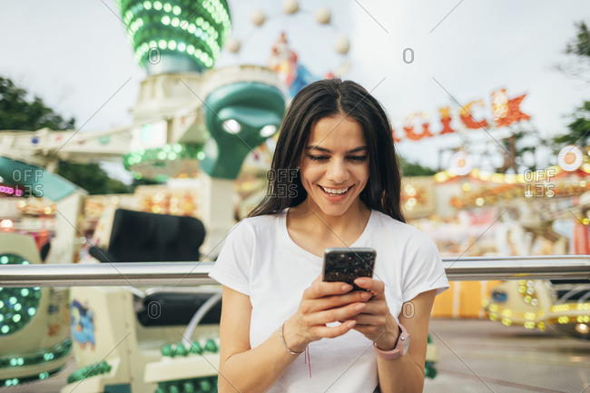 Smiling young woman using smart phone while standing in amusement park