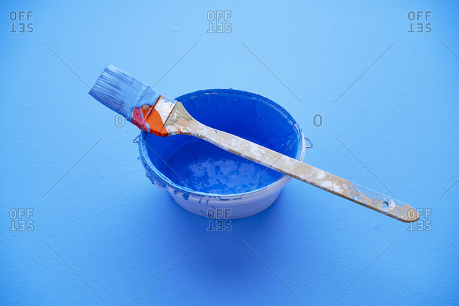 Studio shot of paintbrush on top of bucket with blue paint