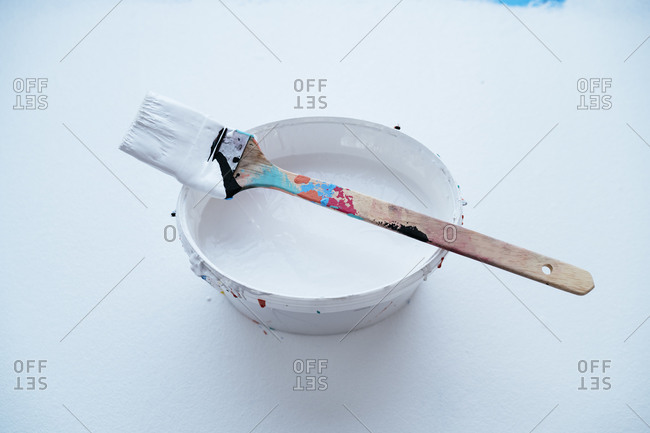 Studio shot of paintbrush on top of bucket with white paint