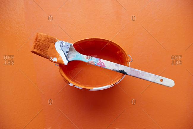 Studio shot of paintbrush on top of bucket with orange paint