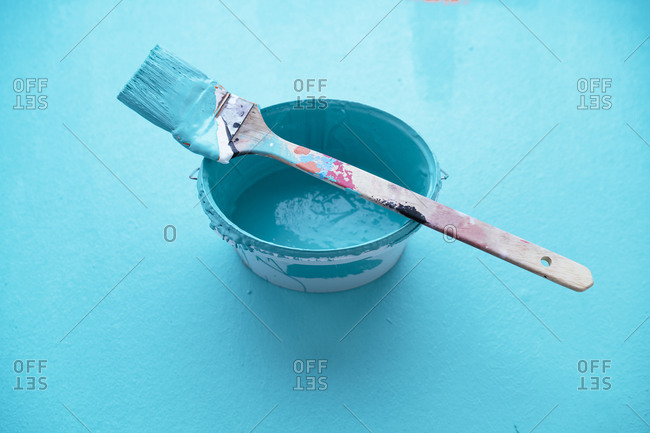 Studio shot of paintbrush on top of bucket with turquoise paint